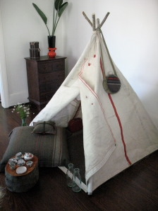 Teepee with army blanket cushions, tea set and vintage blanket covered water bottle